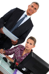 Smiling businessman standing over his overworked assistant