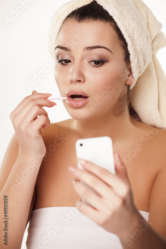 girl  fixes her makeup and uses her smartphone as a mirror
