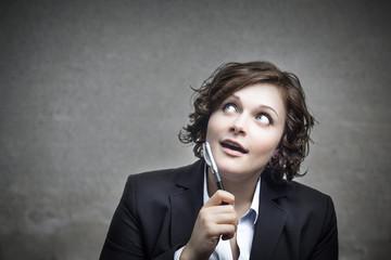 Junge Geschäftsfrau nutzt ihren Denkstift.