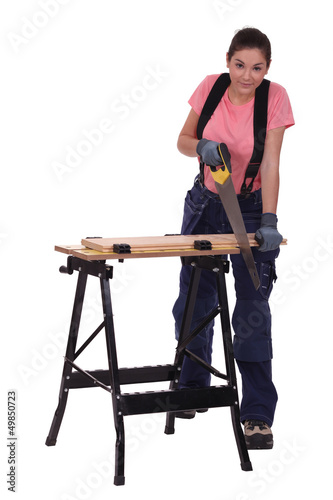 female carpenter sawing a plank