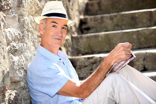 Retired man reading his guidebook