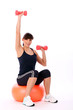 Beautiful woman exercising with fitball and dumbbells