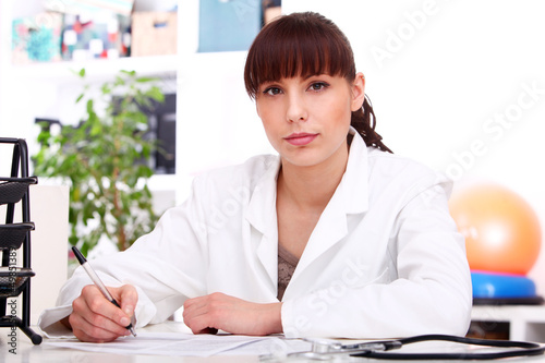Young beautiful doctor at table