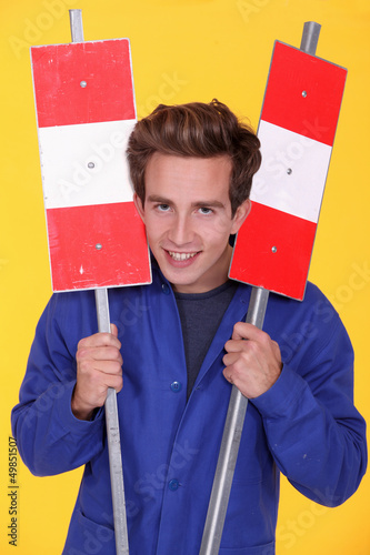 Man holding two metal road signs