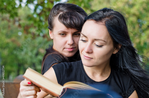 Two women reading a book together