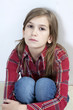 Unhappy little girl sitting on carpet. Problems with parents