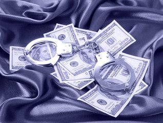 money and handcuffs on blue silk fabric, dollars bills