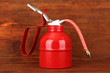 Oil can on wooden background