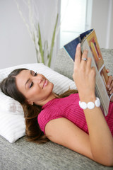 Woman laying reading magazine