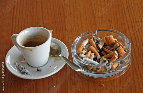 ashtray chock full of cigarette butts and a cup of espresso