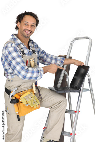 Handyman stood with ladder and pointing at laptop