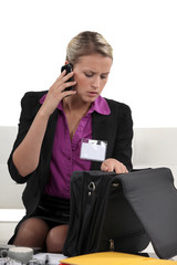 Businesswoman looking through briefcase whilst on the phone