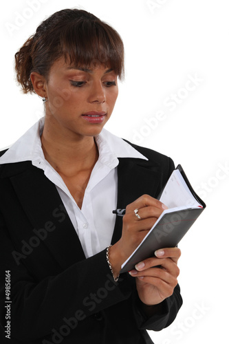 Businesswoman writing in her diary