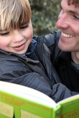 Father and son reading book outdoors