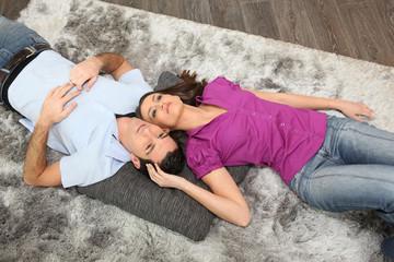 Woman cuddling man laid on a carpet
