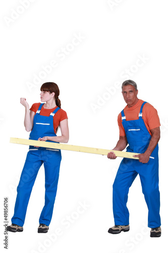 Man and woman holding wood