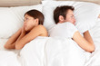 Upset couple with marital problems in bed