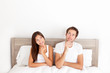 Thinking young couple sitting pensive in bed