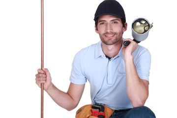 Tradesman holding a copper tube and a blowtorch