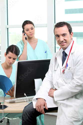 Doctor sitting with nurses at a computer