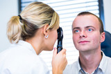 Optometry concept - handsome young man having his eyes examined
