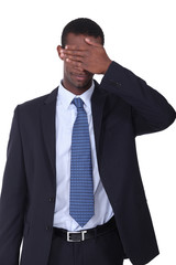 Man in a business suit with his hand covering his eyes