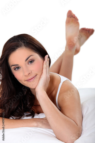 Woman lying on her bed in her underwear