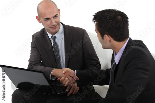 Businessmen shaking hands over a laptop