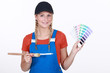 young female painter holding color chart