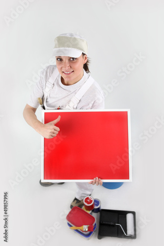 Painter pointing to a blank red sign