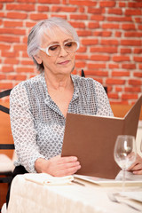 Woman reading menu in restaurant