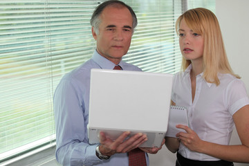 Businessman looking at a laptop with his assistant