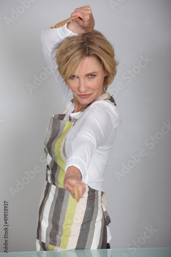 Woman fencing with wooden spoon