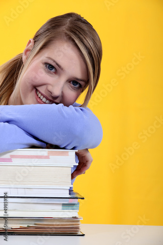 Student leaning on  books