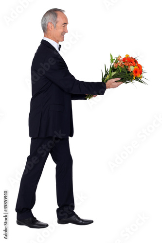 Man dressed in tuxedo holding bunch of lowers