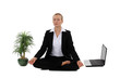 Businesswoman meditating next to her laptop