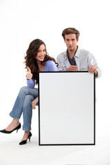 Couple sitting with a blank board