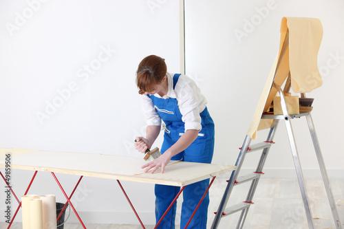 Woman putting up wallpaper