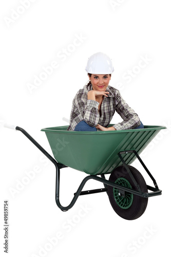 Tradeswoman sitting in a wheelbarrow