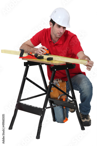 A carpenter taking measures.