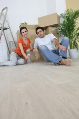Couple sitting on the floor with moving cardboards