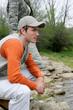 Man sitting at a riverside