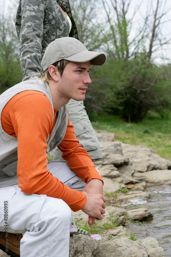 Man sitting at a riverside