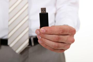 Businessman holding a USB stick