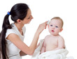 mother is combing baby`s hair after bathing