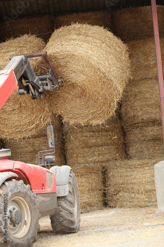 Tractor lifting bail of hay