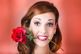 Woman gripping red rose between her teeth