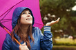Beautiful young woman in raincoat checking for rain.