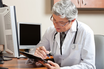Doctor Reading While Sitting At Desk