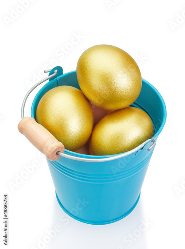 Blue bucket filled with golden Easter eggs. On a white backgroun